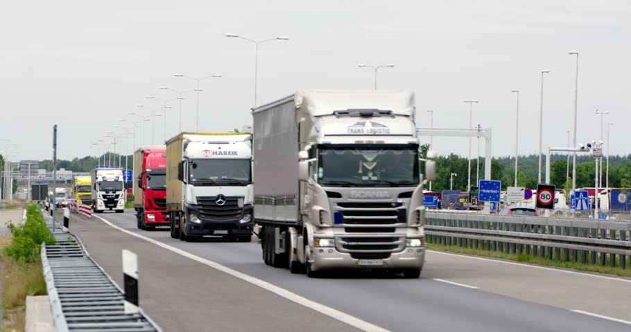 VENLO, NETHERLANDS - MAY 27, 2015: Cars and trucks passing the border to Germany with busy traffic at highway A67 E34, 4K