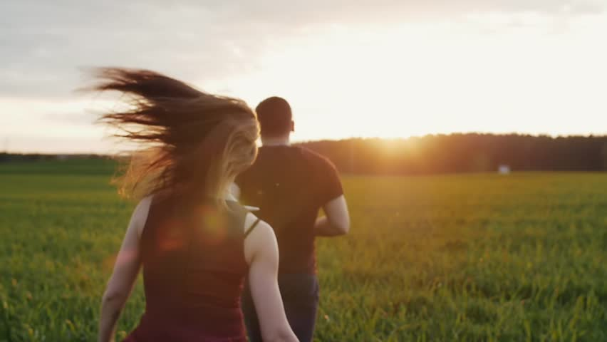 Happy woman chases her man running in field at sunset. Womans hair sway in the wind. Backview, slow mo, steadicam shot #21345334