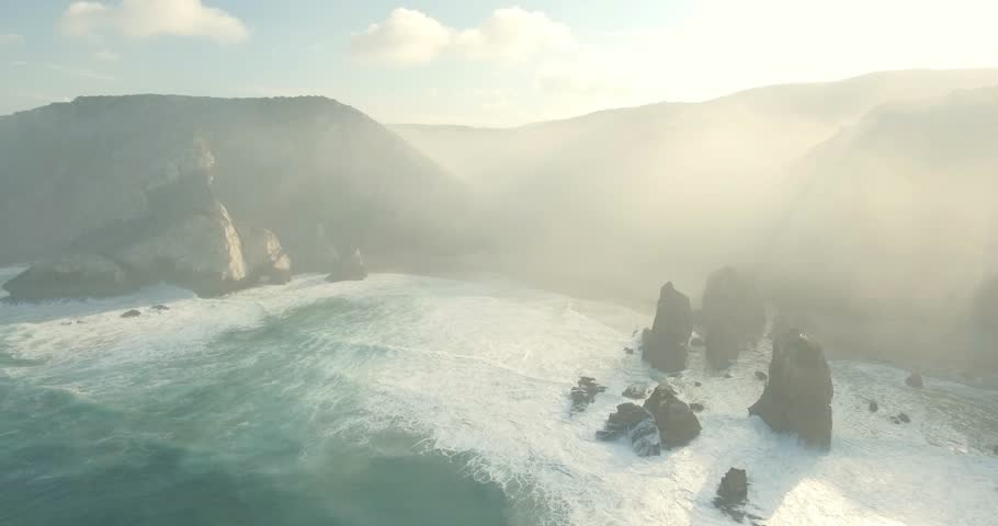 Beautiful aerial or drone shot along the coast of Portugal on a sunny day. Epic cliffs and ocean waves birds eye view during sunrise. Untouched, powerful nature. Cabo da Roca, Portugal Europe. #21359914