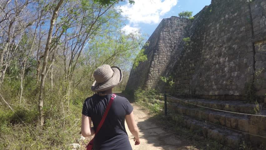 A gimbal shot of tourists walking through the ancient Mayan ruins of Ek Balam near Chichen Itza