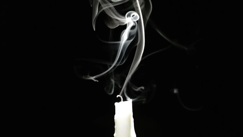 Candle blown out. The candle is lit and extinguished in the dark. White candle. Black background. Slow motion.
