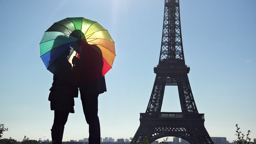 Young woman and man lovers behind colored umbrella in front of Eiffel tower in Paris, playful colored love, romantic destination | Shutterstock HD Video #21396820