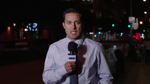 night male news reporter nicely dressed holding NNC microphone city street reporting news story THEN tilt up mid sectiof large modern office building, (Sep 2013)