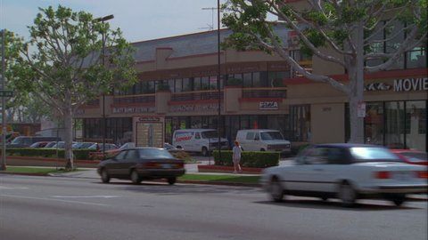 day Wide hold across strip mall then Pan right Raked right Movies More, large corner video store strip mall