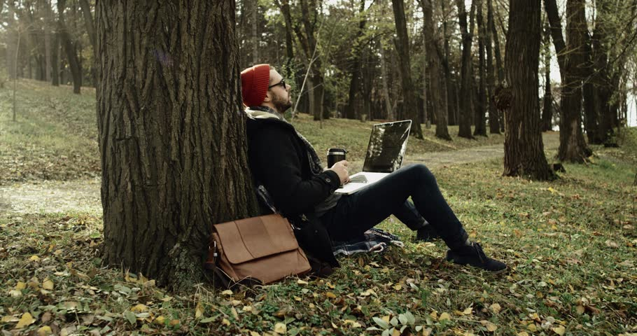 Man in nature park sitting with laptop under a tree and thoughtfully  drink a tea