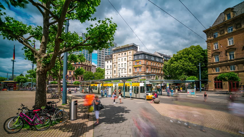 Mainz, Germany - June 22, 2016: Mainz tram and bus stop showing pedestrians and public transport interchange by day in Timelapse