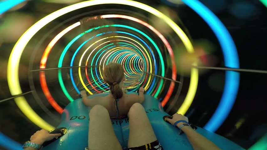 Slope down by water slide in water park. Fun travel inside of the multi color tube at aqua park filmed on action camera. Slow motion. #21455524