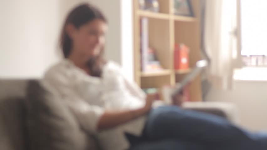 Female sitting on sofa drinking tea and reading on digital tablet