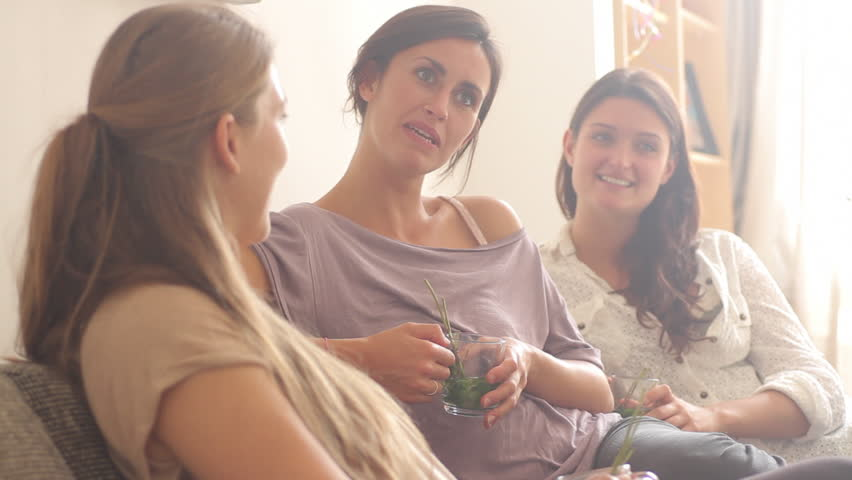 Female friends sitting on sofa drinking tea and chatting