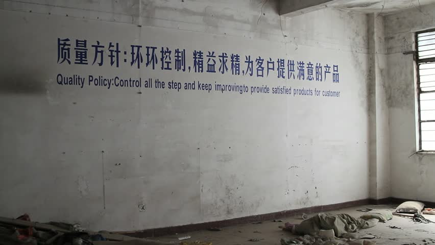 abandoned factory building with ironic quality control reminder painted on the wall
