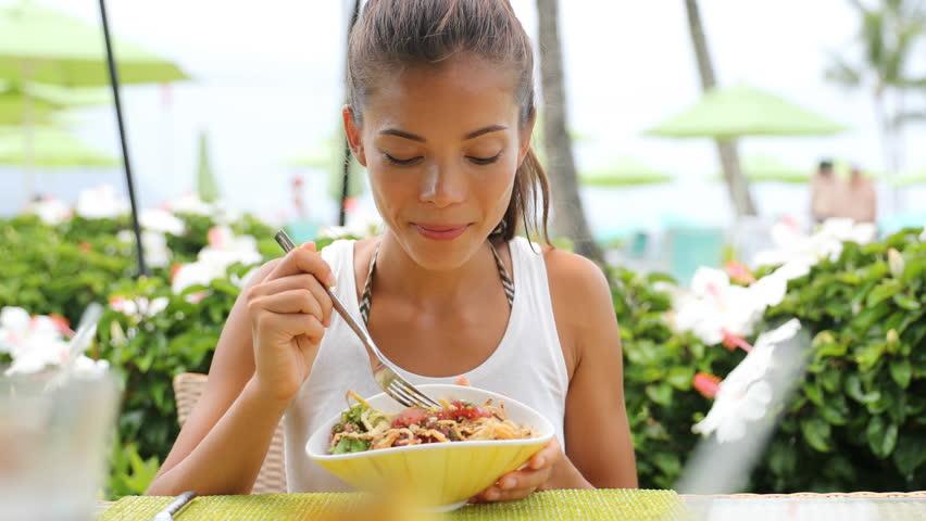 Woman eating a fresh raw tuna dish, hawaiian local food poke bowl, at outdoor restaurant table during summer travel vacation. Hawaii poke bowl food plate. Ahi tuna hawaiian cuisine. 59.94 FPS.