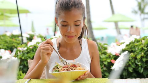 Woman eating a fresh raw tuna dish, hawaiian local food poke bowl, at outdoor restaurant table during summer travel vacation. Hawaii poke bowl food plate. Ahi tuna hawaiian cuisine. 59.94 FPS.