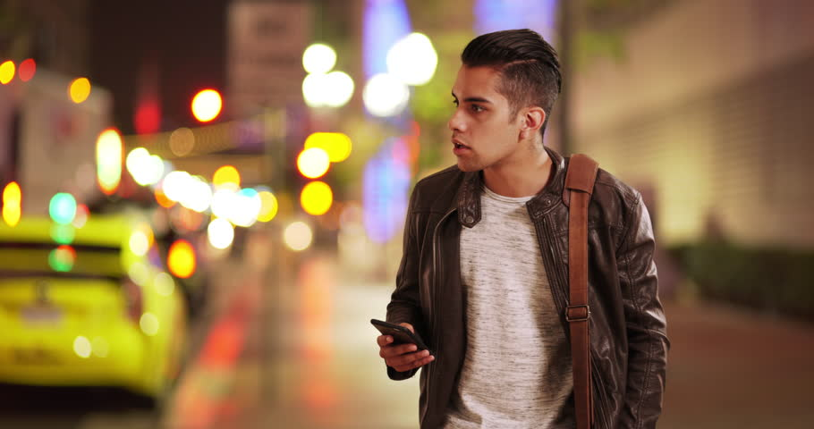 Millennial Latino man calling for taxi or ride sharing service on city street. Hispanic guy at night waiting for uber car with smart phone in hand. 4k