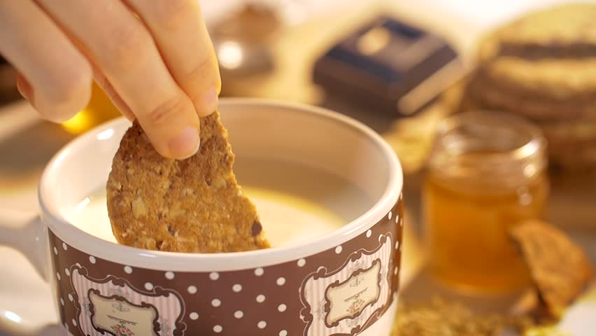 A woman hand dunks a cookie in the milk mug during the breakfast in a warm morning. Slow motion closeup shot
