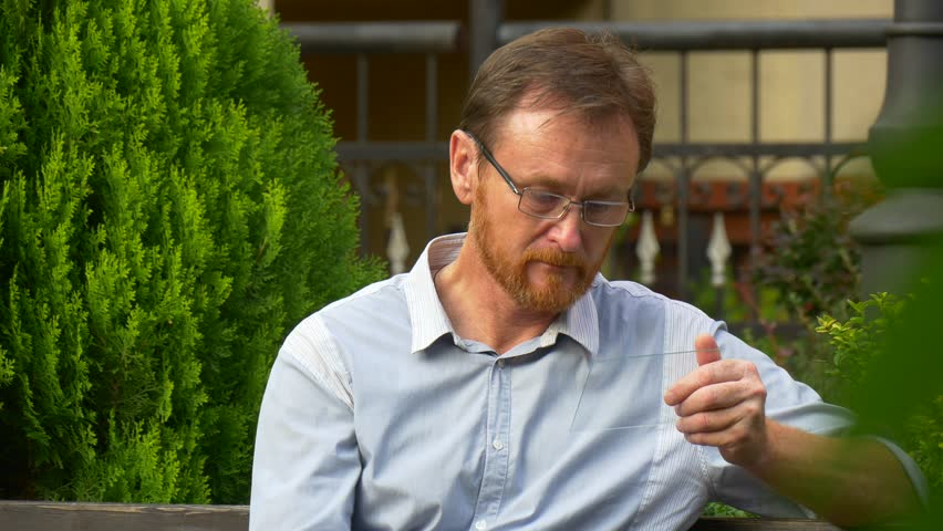 A Adult Red-Haired Man Has a Rest on an Area in a Centre of City Park. he Looks at His New Virtual Smartphone. the Man Watches Exchange Rate of Gold With Its Help. | Shutterstock HD Video #21585964