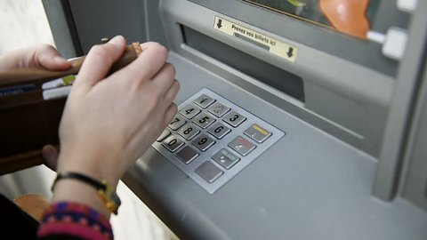 Pressing buttons on keypad of ATM - Closeup of young female hands using and typing on ATM, bank machine for the money withdrawal procedure of available funds in euro, dollars usd pounds currencies