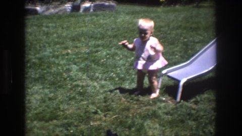 MT BROMLEY VERMONT 1976: baby playing on grass next to slide with man and dog entering the shot