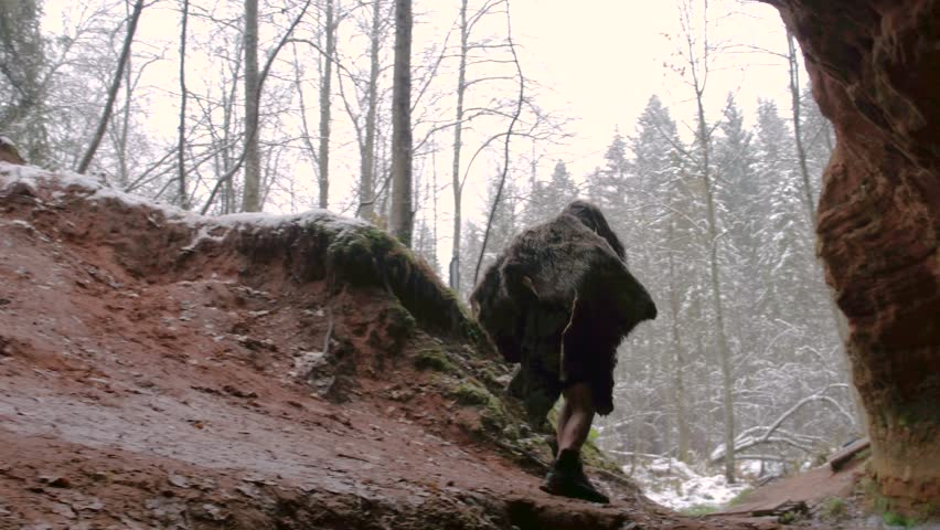 Prehistoric caveman goes outside from his cave on a background of winter forest