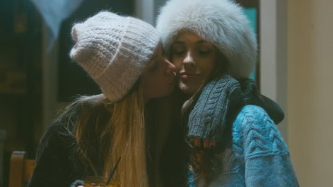 Two cheerful cute teenage girls hugging, one girl kissing her best female friend on the cheek. Two young women in knitted beanies and coats. 60 FPS slow motion, 4K UHD RAW edited footage