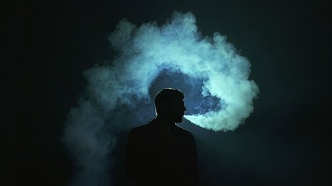 The man exhale electronic cigarette smoke on the dark background. Real time capture
