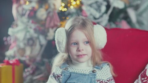 Beautiful little girl gets gifts from the Christmas boxes. Christmas gifts in the boxes for the child. A child enjoys a Christmas gift. The intrigue and joy. Girl looks like a Christmas angel