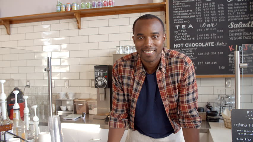 Business owner crosses arms at the counter of coffee shop