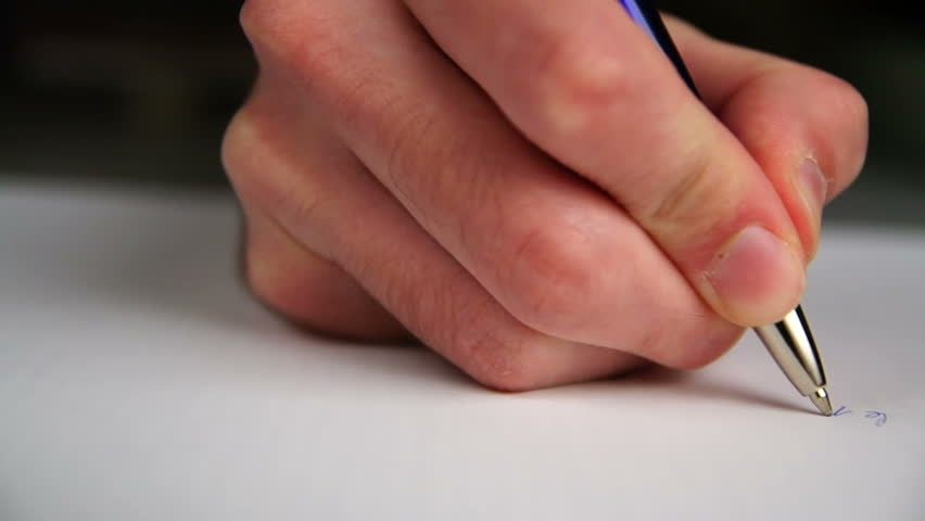 Hand writing a letter on a piece of paper.