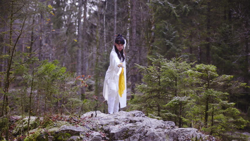 Woman with katana sword stand in a pose on a rock 4K. Long wide shot dolly slide of person on rock in focus with green forest in background. Person wearing white uniform. | Shutterstock HD Video #21680584