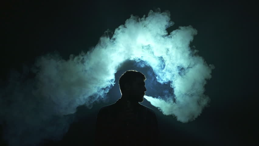 The man smoke electric cigarette on the dark background