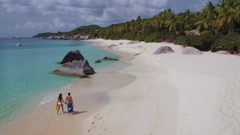 Couple walking on a tropical beach in Virgin Gorda, British Virgin Islands
