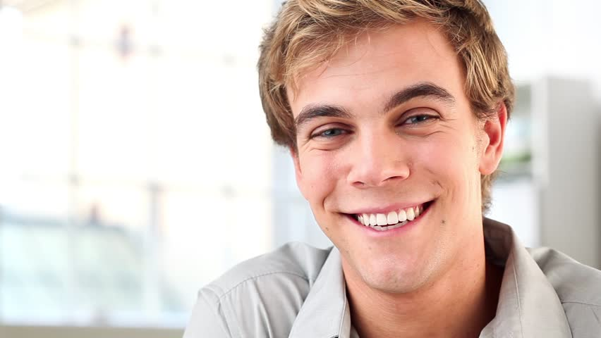 Attractive young man smiling at camera ia happy - indoors