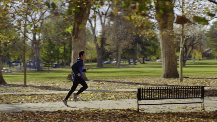 Tracking Shot Of Male Athlete Running Under Falling Leaves On A Treelined Path In The Park (Slow Motion)
