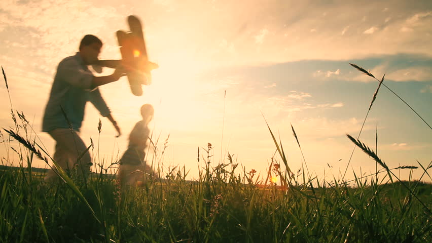 Father and Son are Playing and Running with Model Airplane in the Field. Golden Hour.