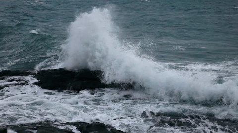 Slow motion, 240fps, of sea wave, swashing against rock. Amazing seascape with green water and white splash and foam. Beautiful natural background for intro in excellent eight times decelerated clip.