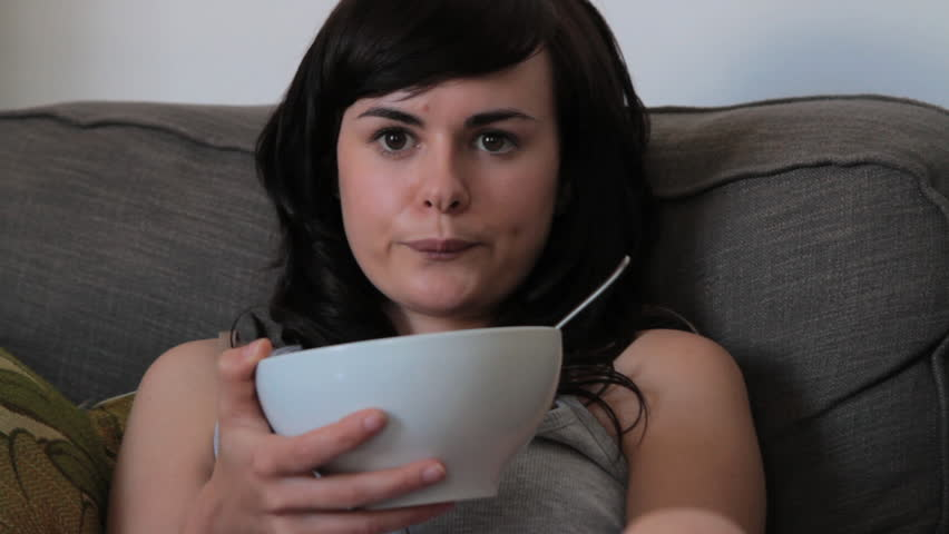 Female eating breakfast on the sofa and watching television