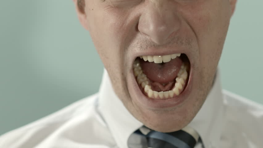 Close-up of angry businessman screaming against blue background. Copy space