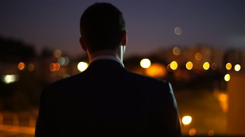 A man on top of a building at night looking to city