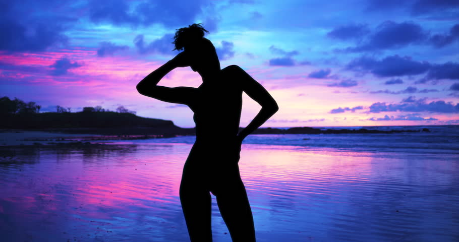 Single silhouette of sensual woman standing on sunset beach of the bahamas. Nude woman isolated on evening beach background.