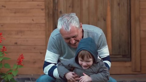 An old man sits near a house, plays with his grandchildren, kisses and hugs them. Kids laugh and have fun. Slow mo