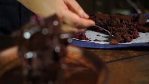 Chocolate cake. Men tasting piece of sweet cake. Brownie cake with cherry berry. Eating tasty chocolate dessert. Brownie dessert on plate