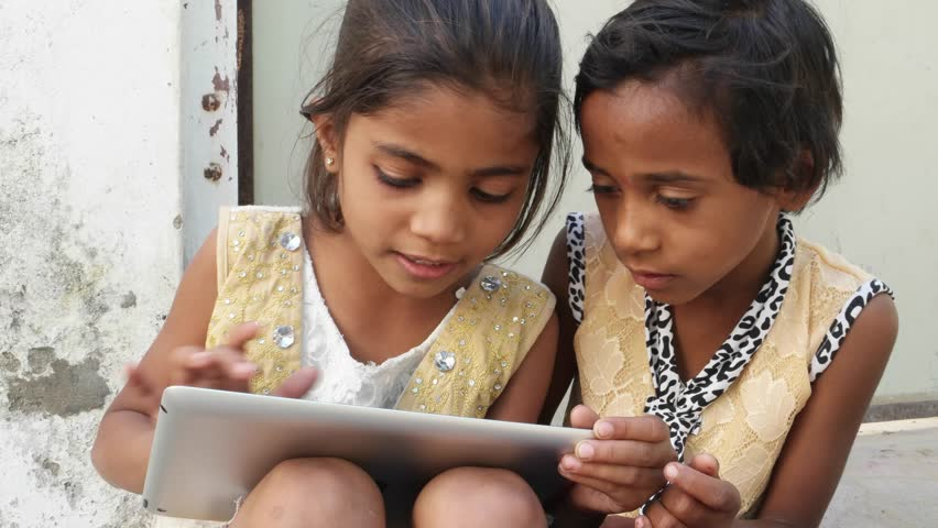 Kids busy working on a touch screen tablet and discussing, India