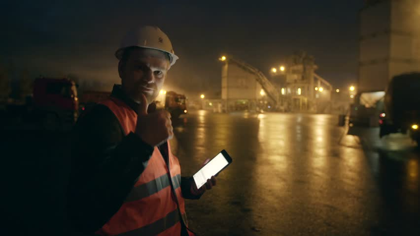 Engineer in helmet with tablet computer looks at camera at heavy industry factory