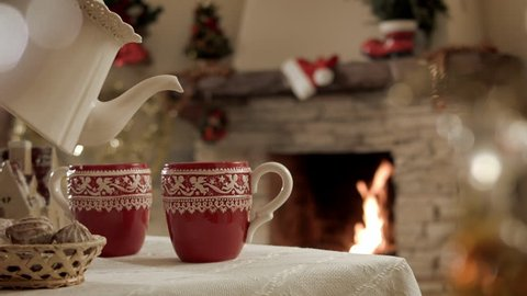 There is a cup of hot tea in a Christmas party on the background of a burning fireplace. Beautiful festive atmosphere