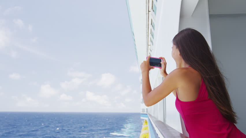 Cruise ship vacation woman taking photo with smart phone camera enjoying travel at sea. Girl using smartphone to take picture of ocean. Woman in dress on luxury cruise liner boat.