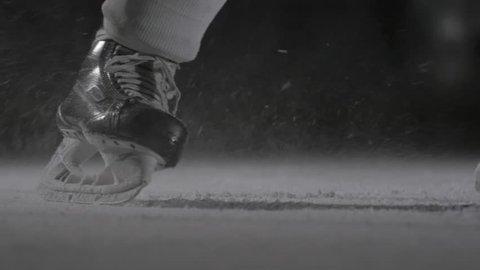 Hockey player make ice sparkles on high speed braking in dark on arena. Motion blur. Legs view only