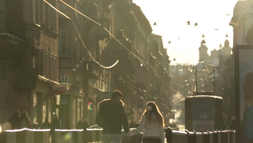 Happy young couple softly kissing and having fun on streets of european city in winter morning. Lviv city, Ukraine