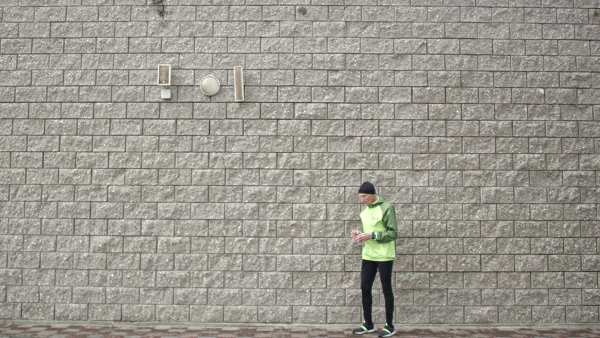 Wide shot of senior man standing against brick wall putting earphones on and then starting running #21950674