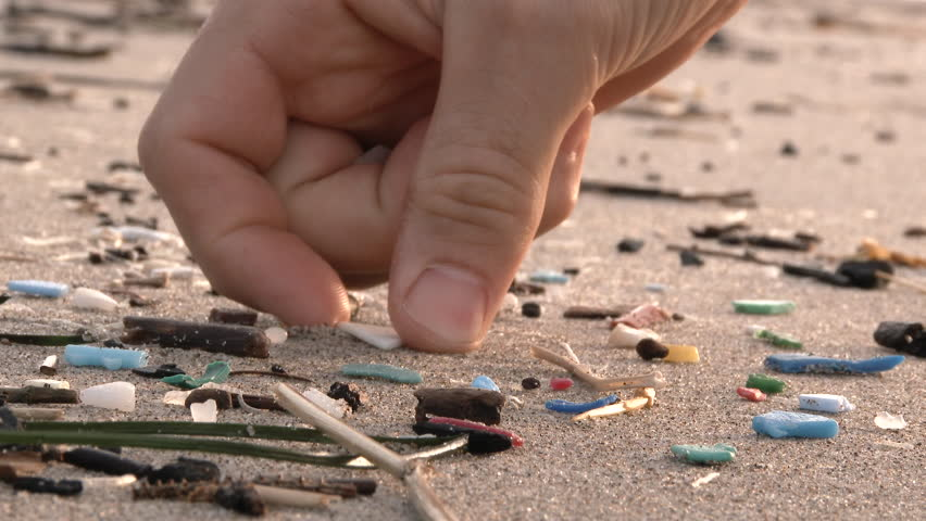 A helping hand picks up micro plastic beach debris washed up from the Pacific Ocean at the Oregon Coast.