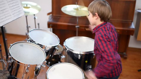 Kid studying drums at school