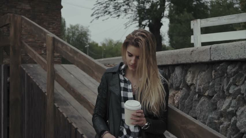 Cute young woman with a cup of coffee outdoor. Slow motion shot of pretty girl enjoying her morning. #22003774